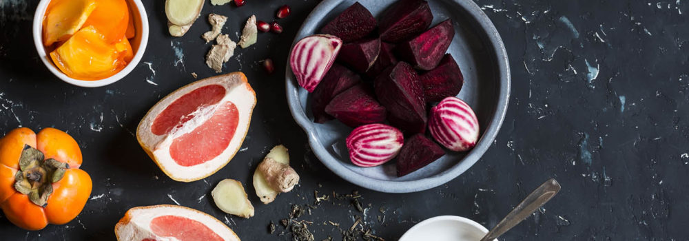 Ingredients for cooking beet and ginger detox elixir. On a dark background, top view